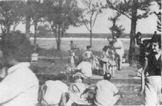 PP Jim Butler is in background in white shirt, with one foot up on a chair.