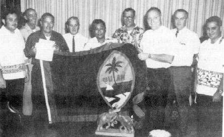 GOVERNOR CARLOS G. CAMACHO presenting members of the Rotary Club of Guam with a Guam Flag for presentation to a Rotary Club in Georgia to fly on the Street of Flags. L to R: PP Jim Underwood, PP Brandenburg, PP Al Minot, PP Jim Bloom, Gov. Camacho, Rtn. Carl Hartzell, Rev. Jordan Peck, PP George Harris, Rtn. Ted Nelson.